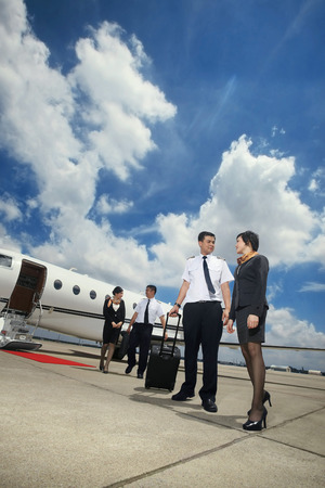 Pilots and flight attendants walking away from private jet photo