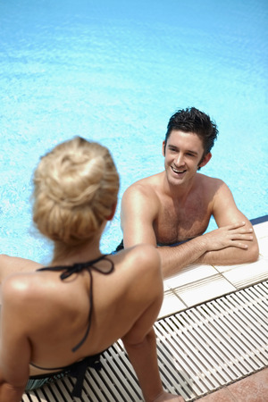 Man and woman talking while relaxing by the poolside photo
