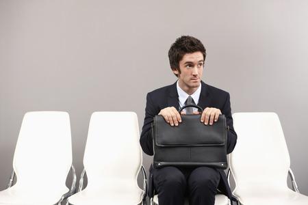 Biznesmen siedzi na krześle, czekając