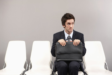 Businessman sitting on chair, waiting photo