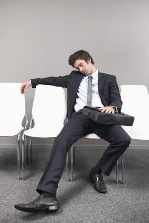 Businessman sitting on chair, sleeping photo