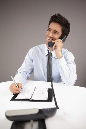 Businessman writing on organizer while talking on the phone photo