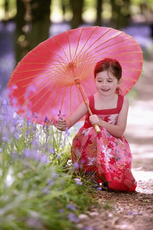 Girl with umbrella looking at flower photo