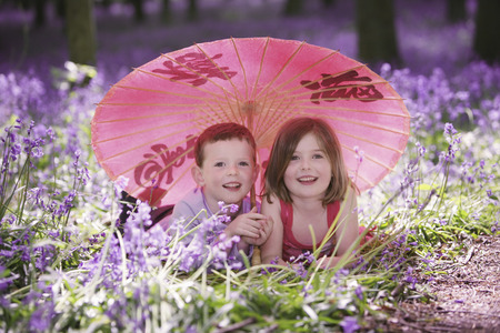Boy and girl lying forward on the ground sharing an umbrella photo
