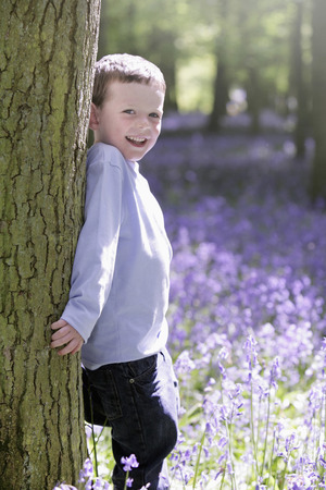 Boy leaning against tree photo