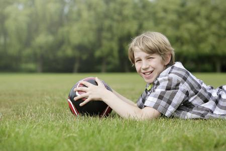 lying forward: Boy with soccer ball lying forward on the field
