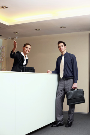 Receptionist giving direction to businessman  photo