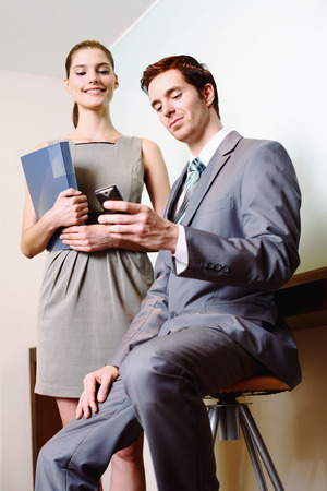 Businessman text messaging on the phone, businesswoman watching photo