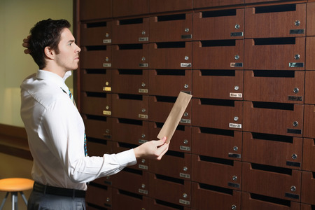 Businessman scratching his head while looking at mailbox photo