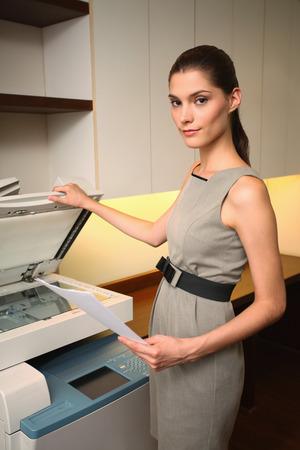 photocopier: Businesswoman using photocopier Stock Photo