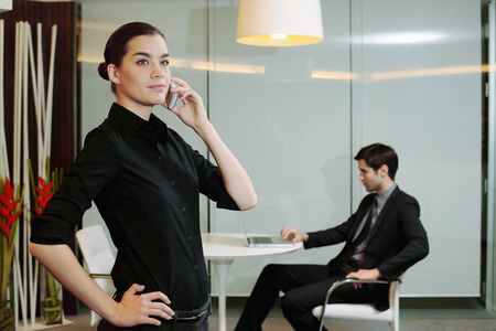 central european ethnicity: Businesswoman talking on the phone, businessman using laptop in the background