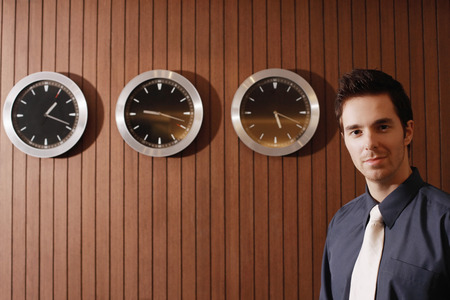 time zone: Businessman with clocks of different time zone on the wall Stock Photo