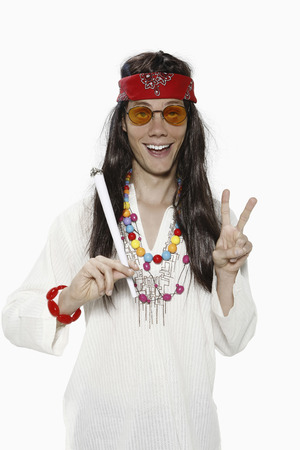 Man dressed up as hippie showing peace sign photo