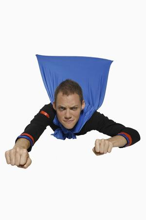 man flying: Man in superhero costume flying
