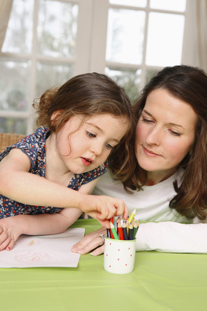 Mother and daughter drawing together photo