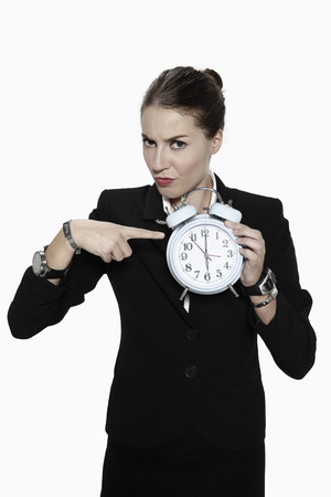 scowl: Businesswoman pointing at alarm clock Stock Photo