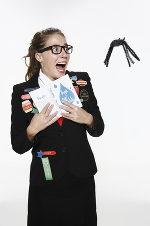 Female student screaming while looking at a dangling spider photo