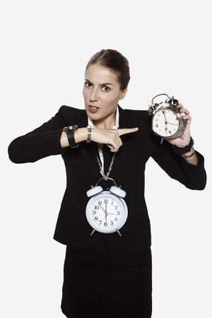 Businesswoman pointing at alarm clock photo