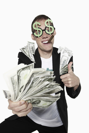 Man with bank notes showing thumbs up photo