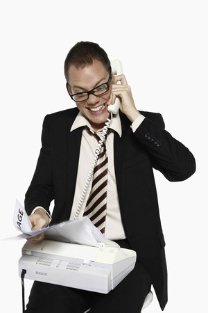 fax machine: Man answering phone call while getting bills from fax machine