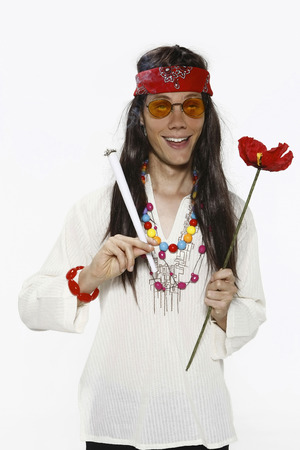 Man dressed up as hippie smoking and holding flower photo