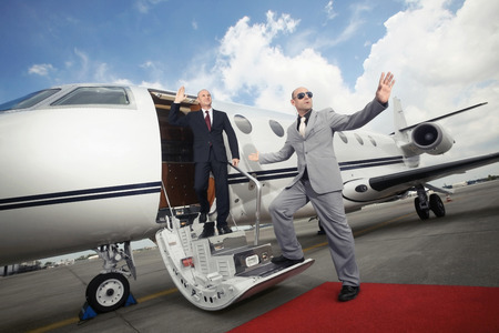 Businessman descending from private jet with his bodyguard photo