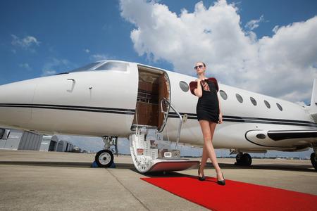 Vrouw die zich op de rode loper bij de prive-jet verlaten