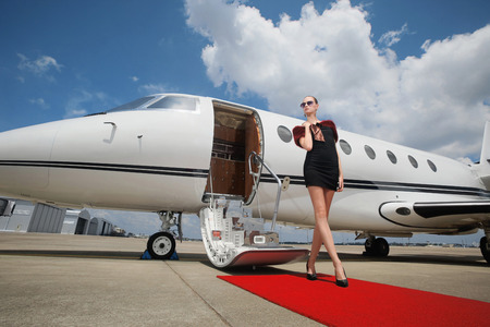 runway: Woman standing on red carpet upon exiting private jet Stock Photo