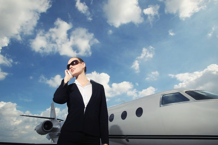 Businesswoman talking on the phone with private jet in the background photo