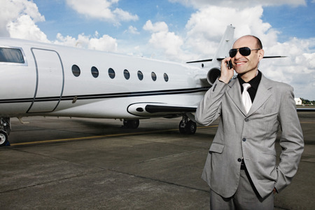 Man talking on the phone with private jet in the background photo