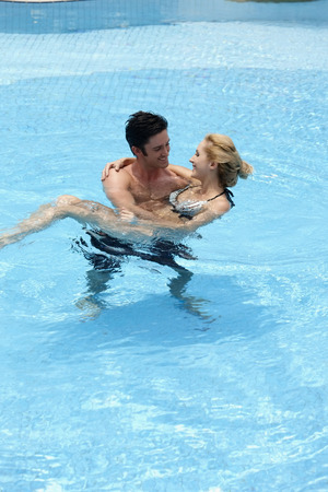 carrying: Man carrying woman in pool
