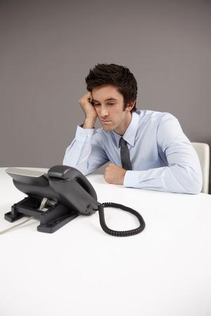businessman waiting call: Businessman sitting beside telephone, waiting for phone call Stock Photo