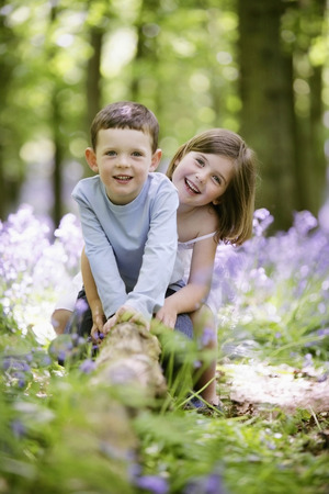 Boy and girl sitting on tree root photo