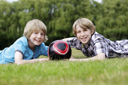 lying forward: Boys with soccer ball lying forward on the field