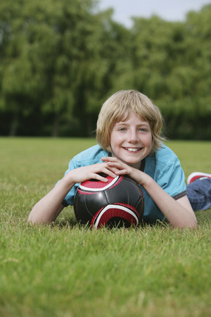 lying forward: Boy lying forward on the field with his football