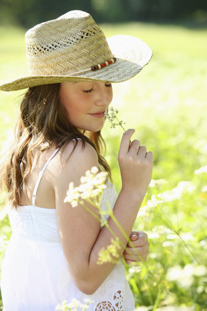 english ethnicity: Girl smelling flowers outdoors Stock Photo