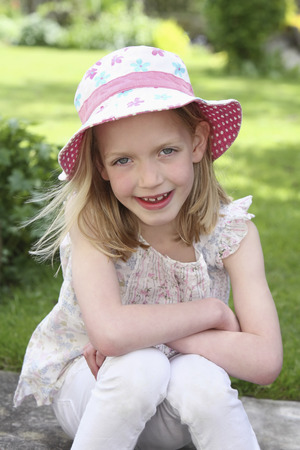 english ethnicity: Girl smiling at the camera while sitting outdoors Stock Photo