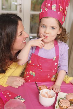 licking finger: Girl licking finger while mother looks on