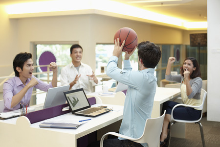 Businessmen playing basketball during work