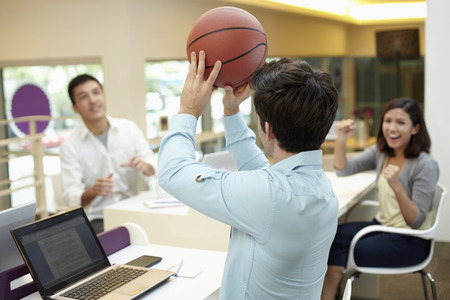 Businessmen playing basketball during work photo