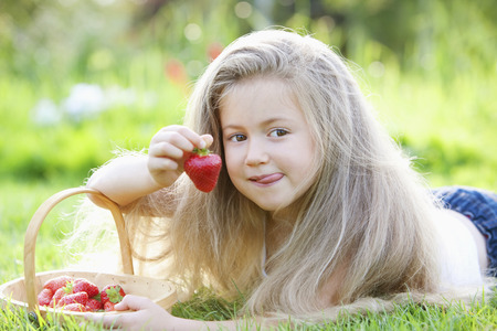 Girl holding a strawberry photo