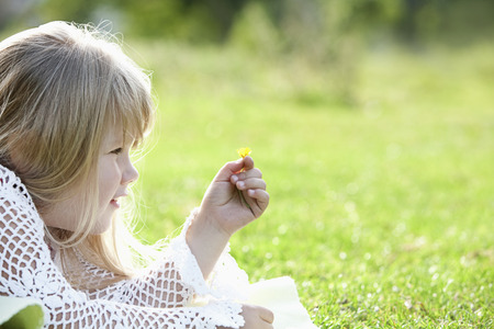 Girl holding a small yellow flower