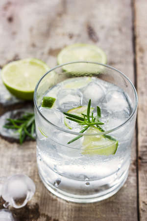 lemon: C�ctel con hielo y rodaja de lim�n sobre fondo de madera