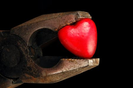 heart squeezed by rusty tool
