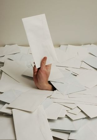heaped: hand with envelope in pile of letters Stock Photo