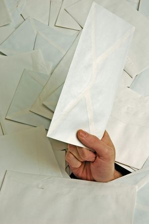 closeup of hand with envelope in pile of letters