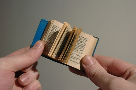 a mini book on hand over faded background