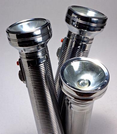 closeup of three metallic flashlights on light background
