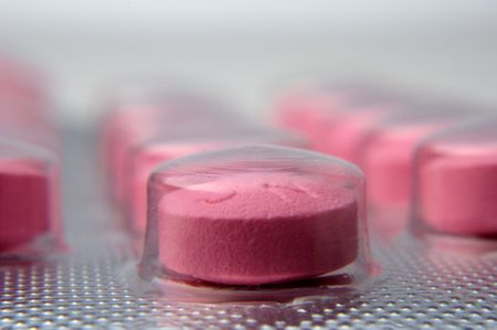 macro view of red pill in plastic blister