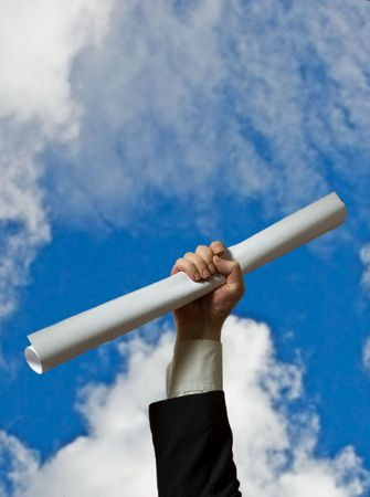 hand holding a white diploma over sky background